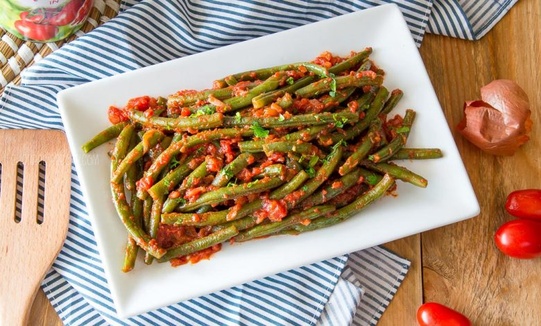 green beans in tomato sauce on a white serving plate