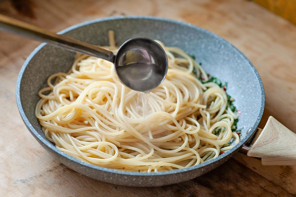 pasta in a pan with a laddle of pasta cooking water